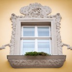 beautiful old stucco work window with flower on facade of old house in europe